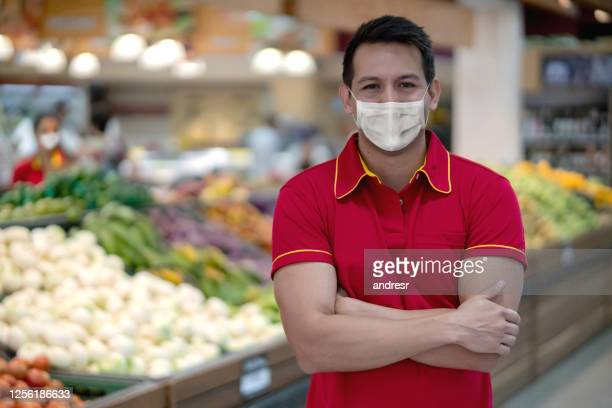 assistant working at a supermarket in the fruit and vegetables section and wearing a facemask - biosecurity stock pictures, royalty-free photos & images