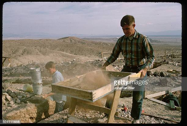 Assistants at the Calico Hills Early Man dig site sift dirt from the trenches above the main pit in search of man made artifacts California 1966
