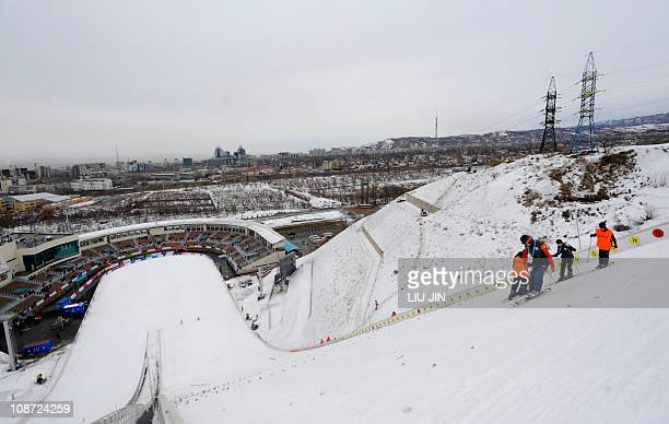 Assistants check the slope before the men's team ski jumping K125 event of the 7th Asian Winter Games at the International Ski Jump Complex in Almaty...