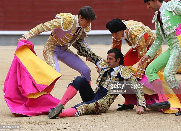 Assistants help Spanish matador David Mora after he was injured during a bullfight of the San Isidro Feria at the Las Ventas bullring in Madrid on...