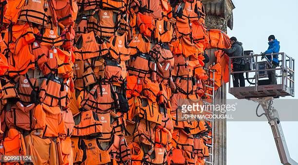 Assistants of Chinese artist Ai Wei Wei decorate the columns of Berlin's Konzerthaus with lifejackets on February 13 as part of an installation...