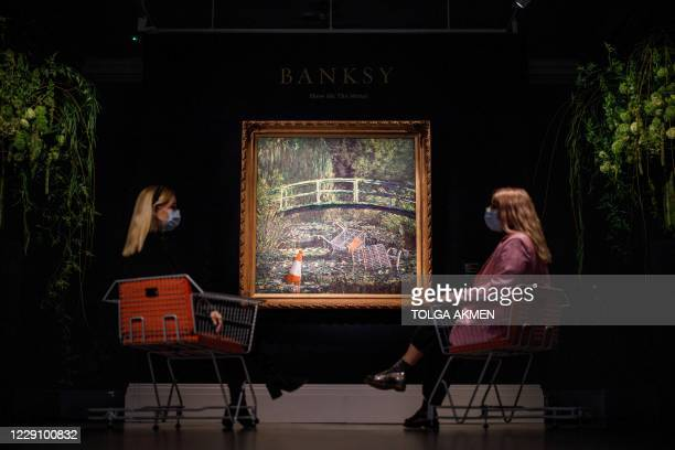 Assistants pose by an artwork entitled Show me the Monet by British street artist Banksy during a photo call for Major Contemporary Art Auction at...