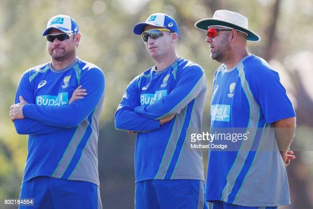 Assistants Ryan Harris and Brad Haddin with head coach Darren Lehmann signs autographs for fans during day three of the Australian Test cricket...