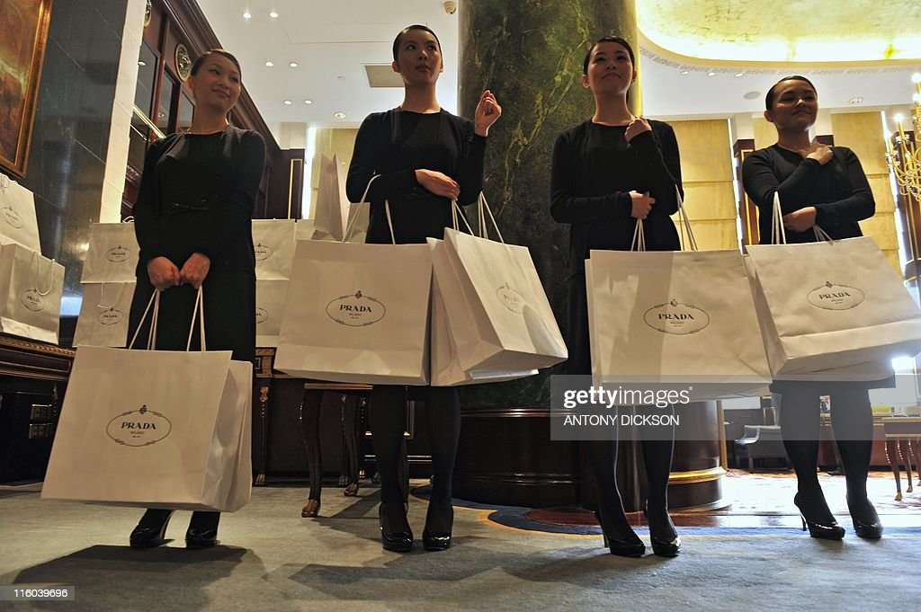 Assistants stand with Prada bags during : News Photo