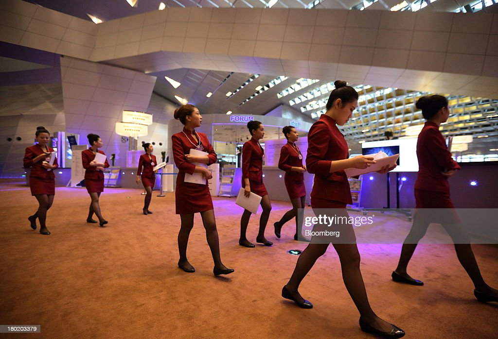 Assistants walk through the Dalian International Conference Center in Dalian, China, on Tuesday, Sept. 10, 2013. The World Economic Forum Annual Meeting Of The New Champions 2013 will be held in Dalian from Sept. 11 to 13. Photographer: Tomohiro Ohsumi/Bloomberg via Getty Images