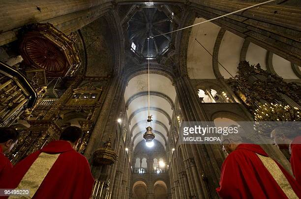 Assistants walk under the Botafumeiro the world's biggest thurible at the Cathedral of Santiago de Compostela northwestern Spain on December 30...