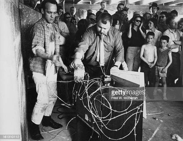 Assisted by American artist Al Hansen German artist Wolf Vostell wraps a television set in barbed wire during a 'happening' at sculptor George...