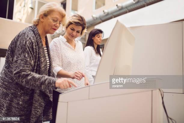 Asistencia a senio mujer en cajero automático
