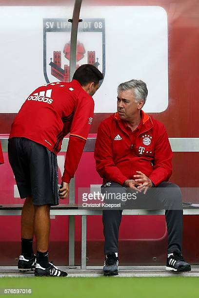 Assitant coach Davide Ancelotti speaks to father and head coach Carlo Ancelotti of Bayern Muenchen stand on the bench during the friendly match...
