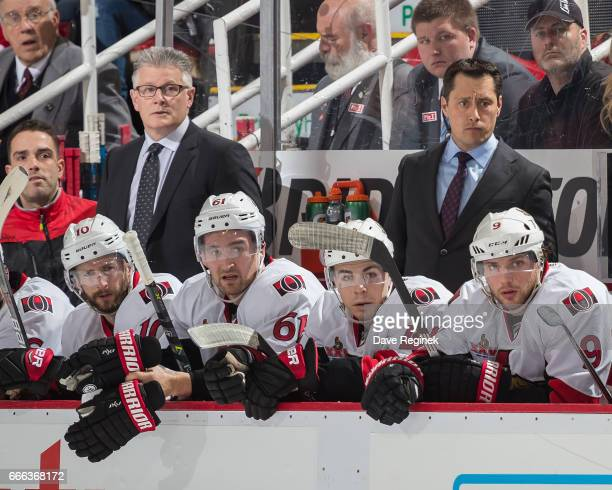Associate coach Marc Crawford and head coach Guy Boucher of the Ottawa Senators watches the action from the bench during an NHL game against the...