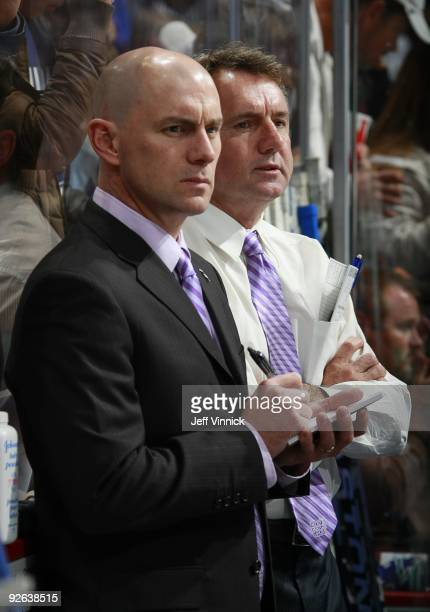 Associate coach Rick Bowness and assistant coach Darryl Williams of the Vancouver Canucks look on from the bench during their game against the...