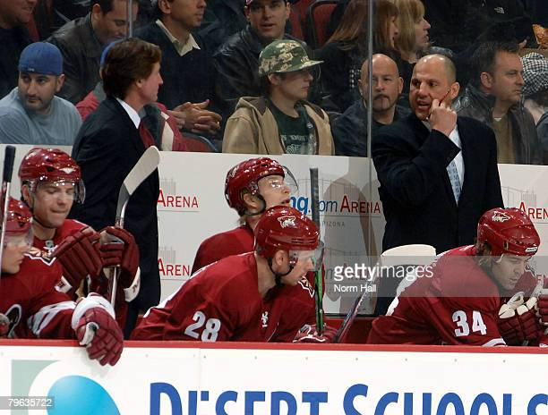 Associate Coach Rick Tocchet in his first game back talks to Wayne Gretzky from behind the Phoenix Coyotes bench during a game against the Columbus...