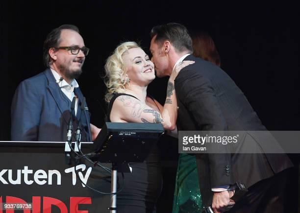 Associate Editor Chris Hewitt and EditorinChief Terri White welcome actor Hugh Jackman winner of the Best Actor award on stage during the Rakuten TV...
