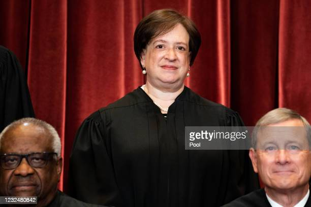 Associate Justice Elena Kagan, with Associate Justice Clarence Thomas and Chief Justice John Roberts in front of her, stands during a group photo of...