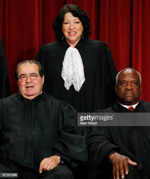Associate Justice Sonia Sotomayor is flanked by Associate Justice Antonin Scalia and Associate Justice Clarence Thomas while taking a group...