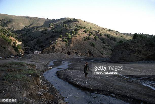 Associated Press reporter and stringer Patrick O'Donnell walks up a riverbed outside of the Zhawar training camp built and controlled by Afghan...