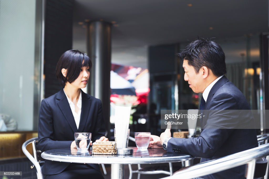 Associates meeting at an outdoor cafe for a meeting : Stock Photo