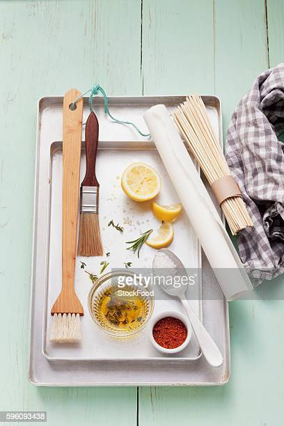 Assorted barbecue utensils, seasonings, lemons and olive oil on a grill pan