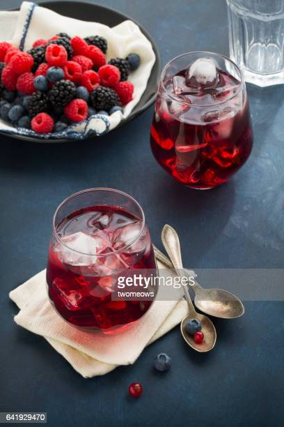 Assorted berry fruits and juice on moody background.