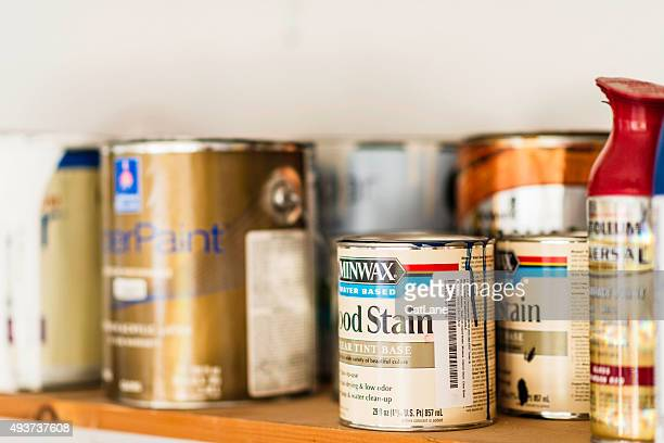 Assorted cans of paint, spray paint and wood stain.