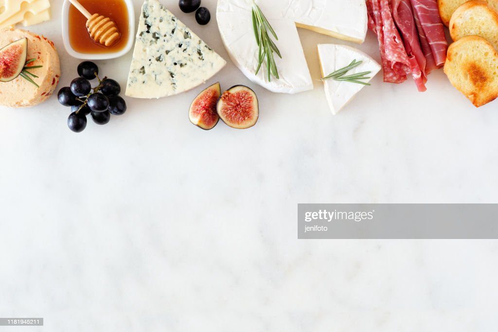 Assorted cheeses and meat appetizers, overhead view top border on a white marble background with copy space : Stock Photo