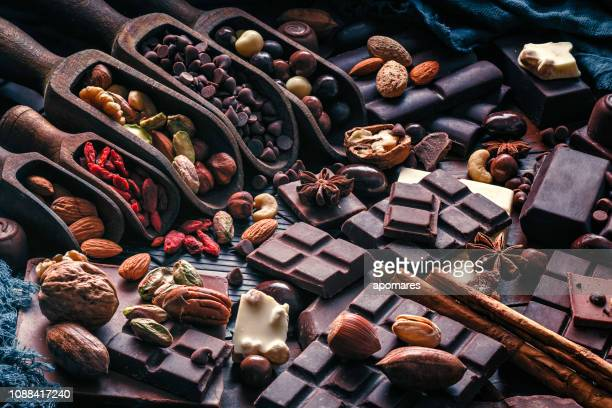 assorted chocolate, nuts and dried fruit in old fashioned style - chocolate stock pictures, royalty-free photos & images