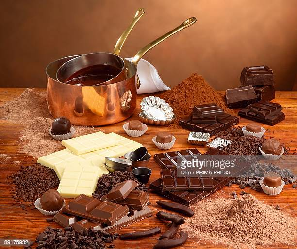 Assorted chocolates with cocoa powder and saucepans