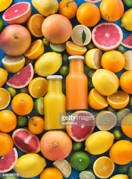 Assorted citrus fruits and juice in bottles.