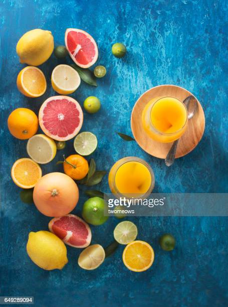 Assorted citrus fruits and juice on blue background.