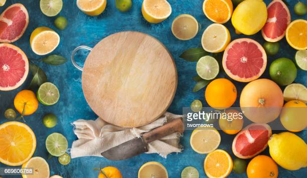 Assorted citrus fruits and wooden cutting board.