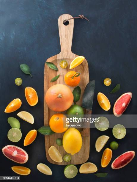 Assorted citrus fruits on wooden cutting board.