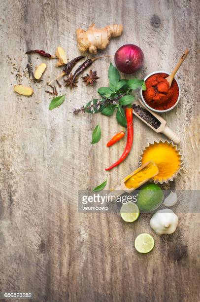 Assorted colourful herbs and spices on rustic wooden background.