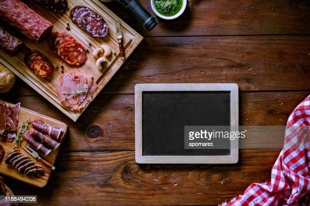 assorted cured ham legs and cheese delicious appetizer on rustic wood table with copy space in a frame - copy space imagens e fotografias de stock
