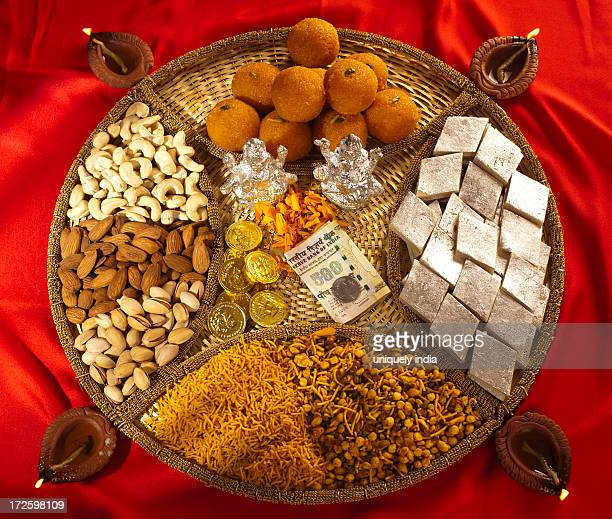 assorted diwali sweets and snacks with diwali diyas - diwali sweets stock photos and pictures