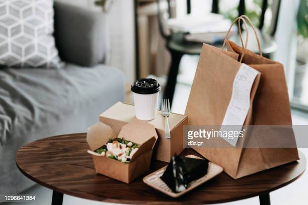 assorted fresh and healthy takeaway meals delivered at home, with healthy grilled chicken vegetable salad, japanese style rice ball / onigiri and a cup of coffee freshly served on the coffee table - 体への関心 ストックフォトと画像