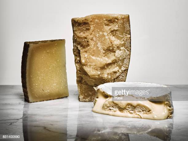 Assorted gourmet cheese on marble surface on light background.