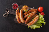 Assorted grilled delicious sausages on a wooden kitchen Board. Copy space. Top view