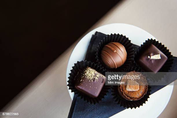 Assorted hand made chocolates on a plate. Overhead view.