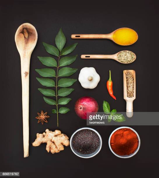 assorted herbs and spices on black background. - curry powder stock photos and pictures