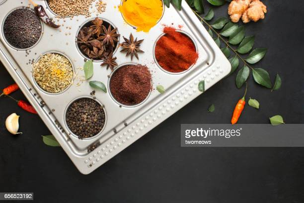 Assorted herbs and spices on rustic black background.