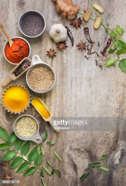 Assorted herbs and spices on rustic wooden background.