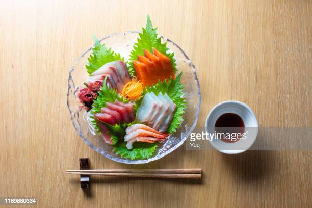 assorted japanese food and sashimi. tuna, yellowtail, sea bream, salmon, sweet shrimp. it is placed on shredded radish and perilla leaves. on the table are chopsticks and soy sauce. - shiso stock pictures, royalty-free photos & images