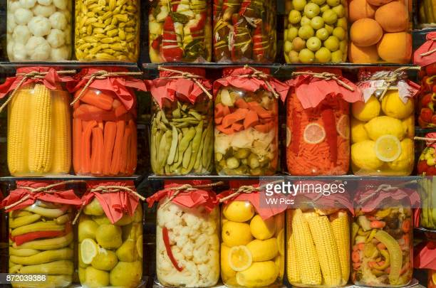 Assorted jars of pickled fruit and vegetables on display in a shop window in Istanbul