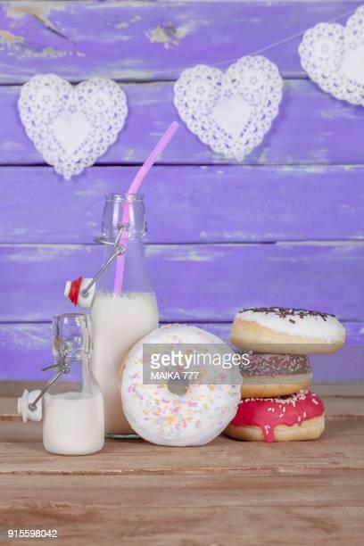 Assorted of Doughnuts and milk in flip-top bottles