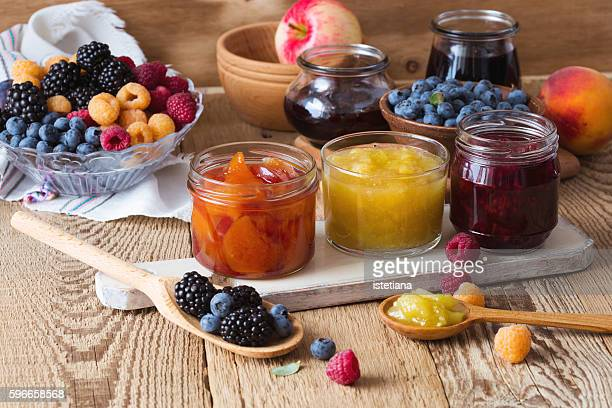 Assorted of homemade jam and  ripe fruits and berries on  rustic wooden table. Peach, apple, rasberry, blueberry and blackberry confiture in glass jars