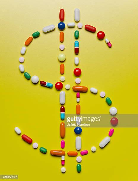 assorted pills creating dollar symbol - currency symbol stock pictures, royalty-free photos & images