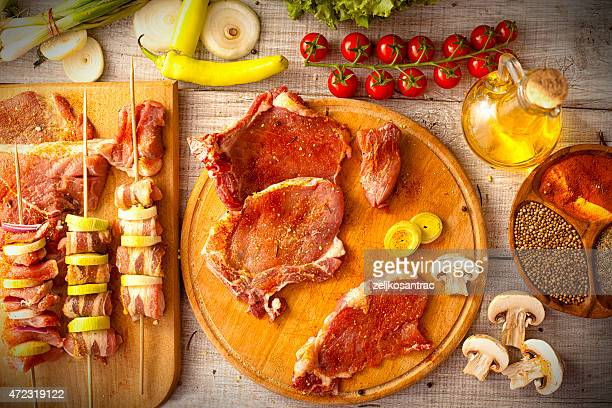 Assorted raw meats and vegetables on skewers and platters