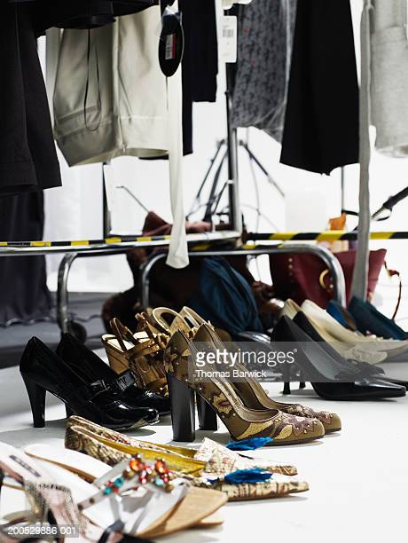 Assorted shoes beneath clothes rack backstage at fashion show