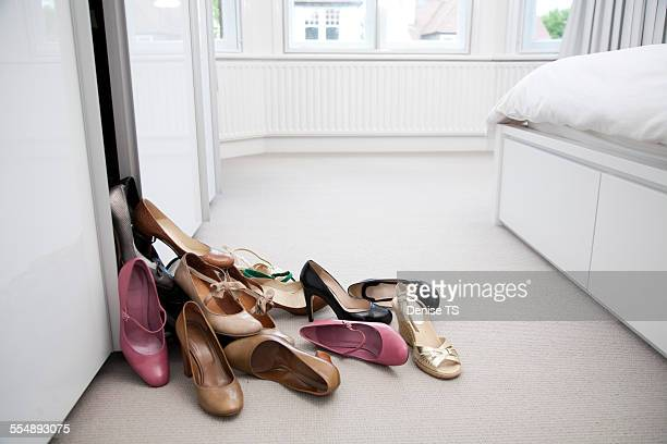assorted shoes falling out of a wardrobe - excesso imagens e fotografias de stock