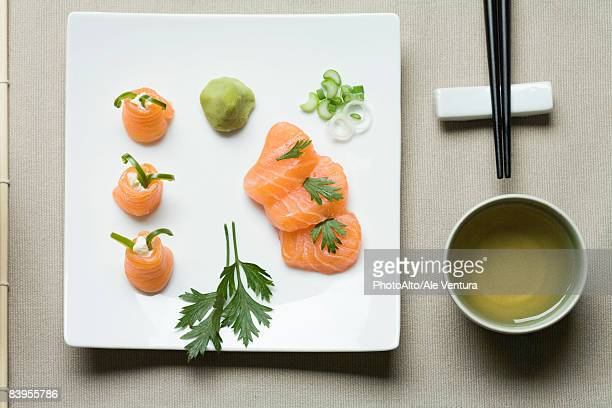 assorted sushi arranged on large sushi plate with tea and chopsticks alongside - wasabi sauce stock pictures, royalty-free photos & images